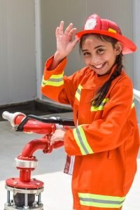 little girl in a fireman hat