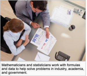 A mathematician is working at a desk and showing a colorful spreadsheet with charts and graphs to a woman sitting at the desk.