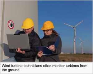 Professional Wind Turbine Technicians look at a computer as they monitor a turbine we see behind them.